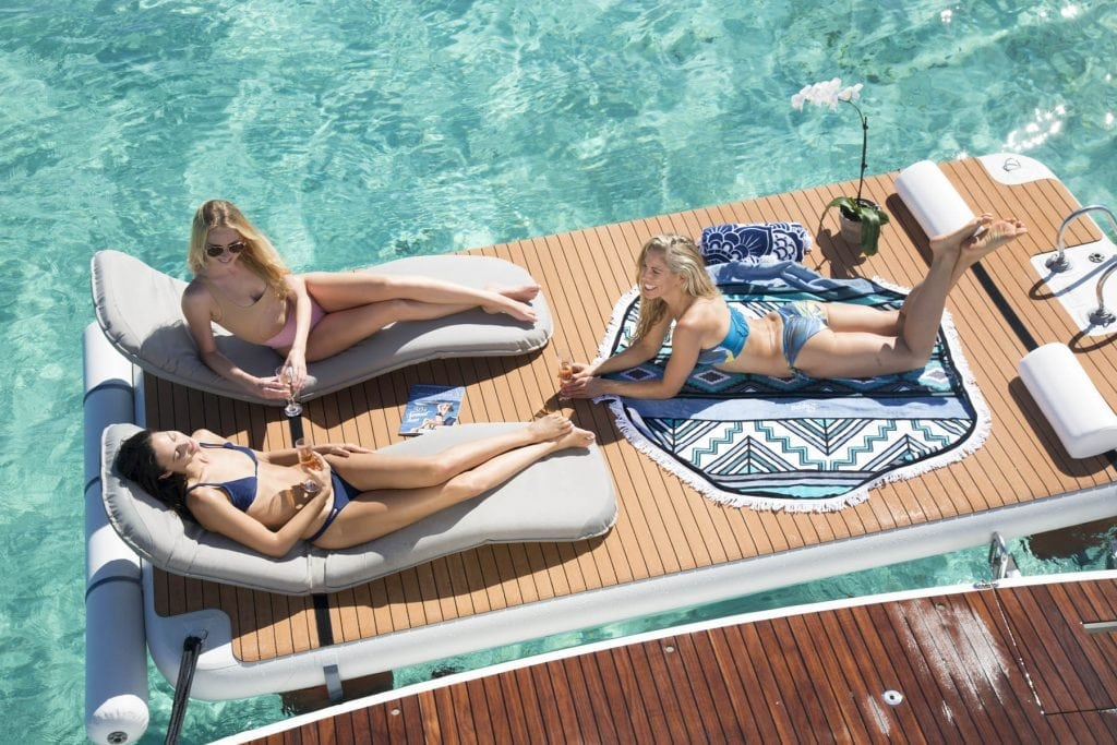 Models from the 2018 Swimsuit shoot lounge on a Nautibuoy Marine Platform in Honeymoon Harbour