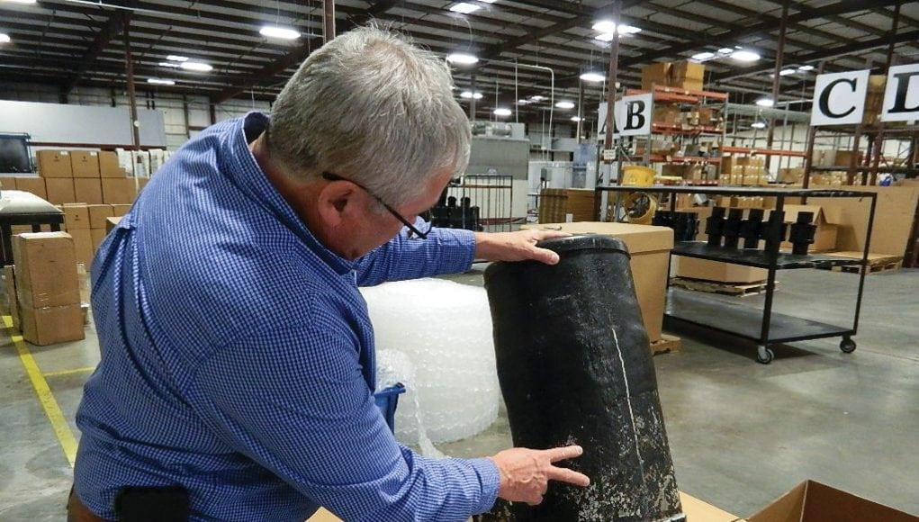 An image of a man holding a piece of his exhaust system