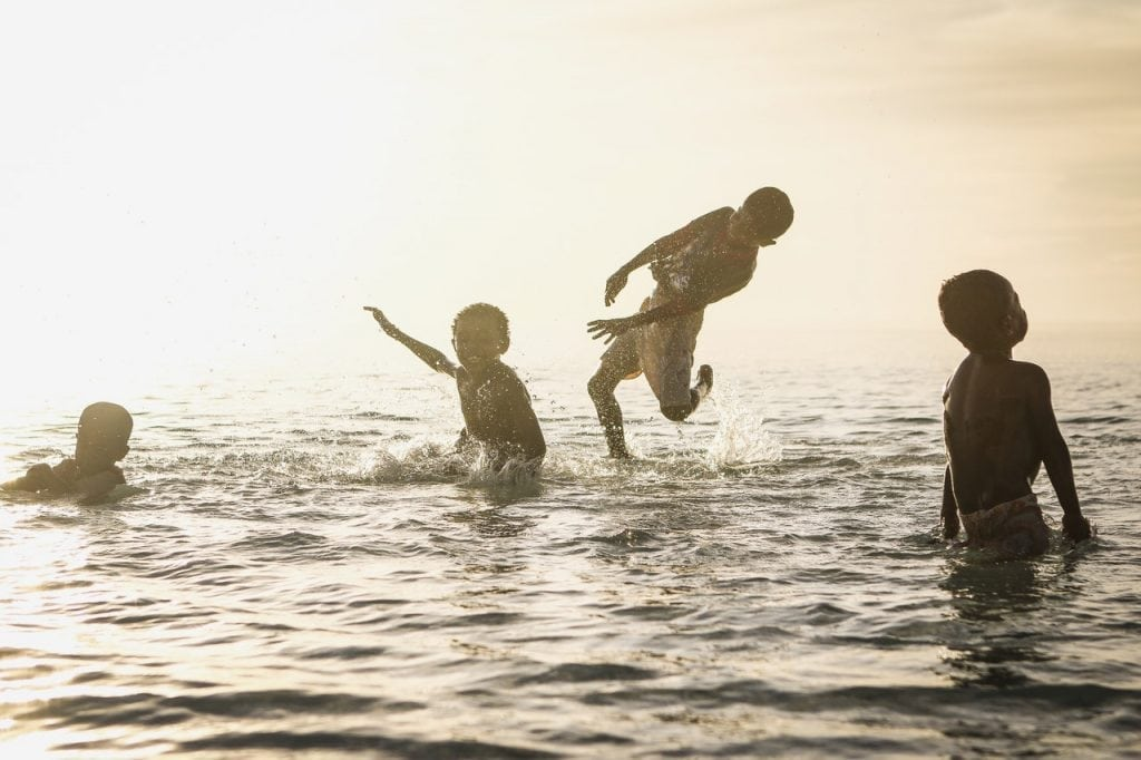 an image of child plaing in the water Rip Currents