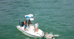 an image of a man falling off a boat while fishing, major fishing fails